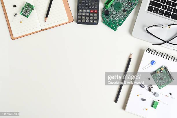 Overhead View Electronic Engineer Office Desk Working with Circuit Board, Laptop, Calculator, electronic components