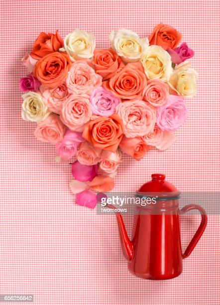Overhead view heart shape rose bouquet flowing out of a teapot.