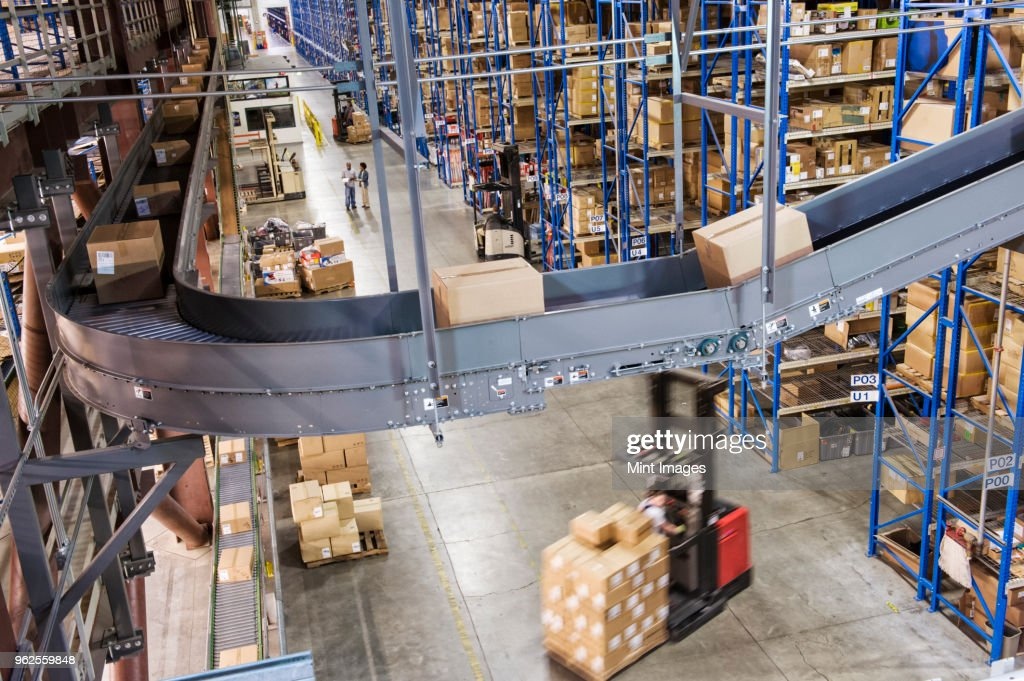 Overhead view looking down an aisle of large racks, conveyor belts and fork lifts, in a distribution warehouse of cardboard boxes holding products. : Stock Photo