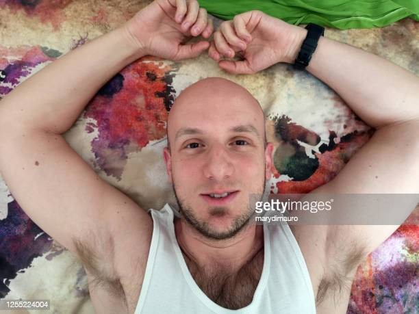 overhead view of a bald man lying on a rug - armpit hair stock pictures, royalty-free photos & images