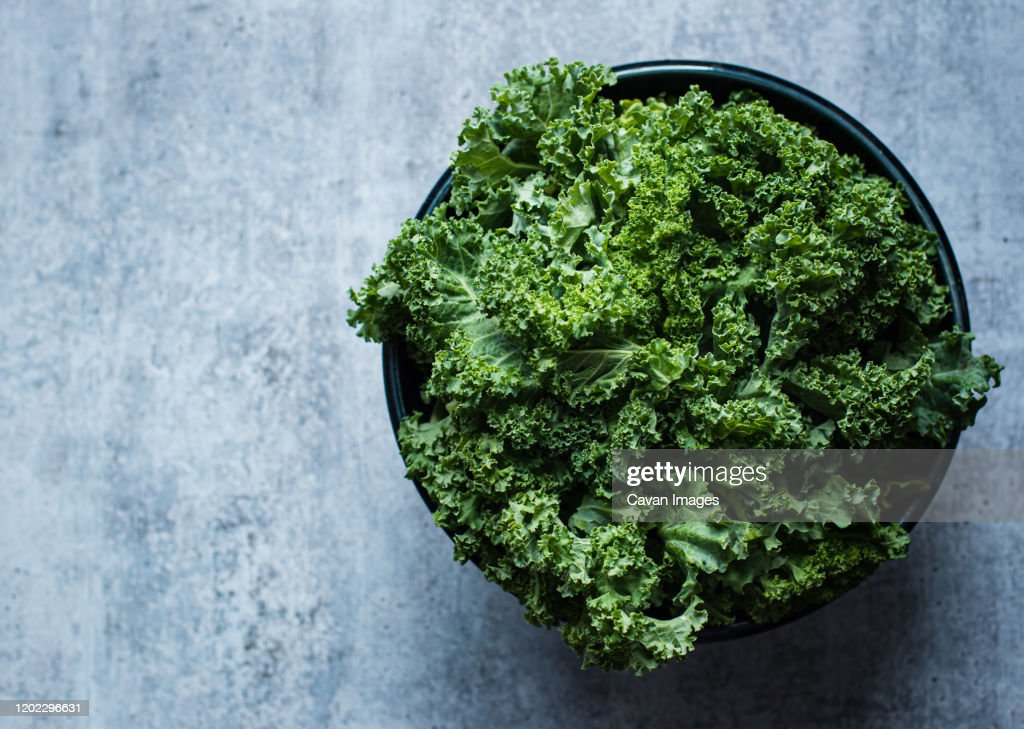Overhead view of a bowl of kale against a gray cement counter. : Stockfoto