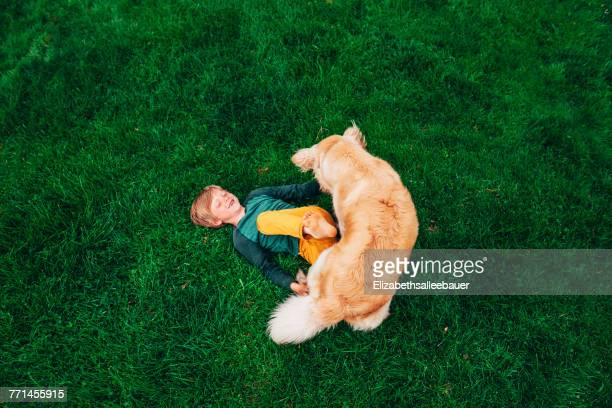 Overhead view of a boy lying on the grass playing with his golden retriever dog
