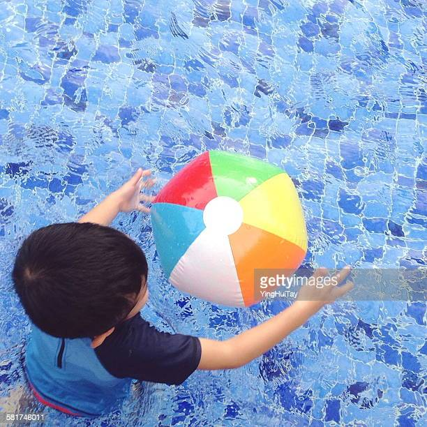 Overhead view of a boy playing with a beach ball in the swimming pool