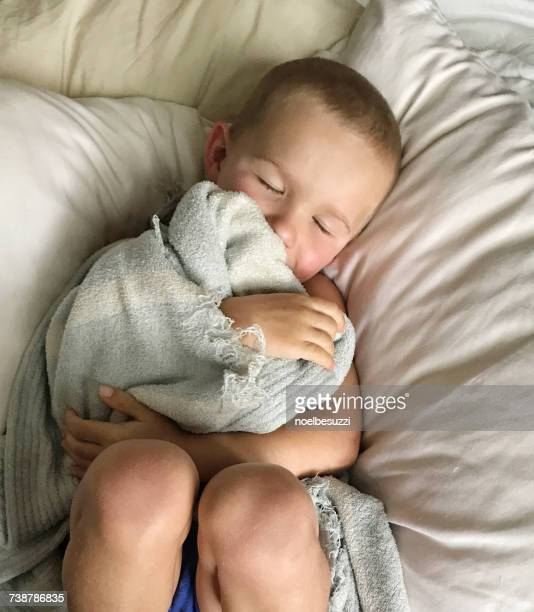 Overhead view of a boy sleeping with his blanket
