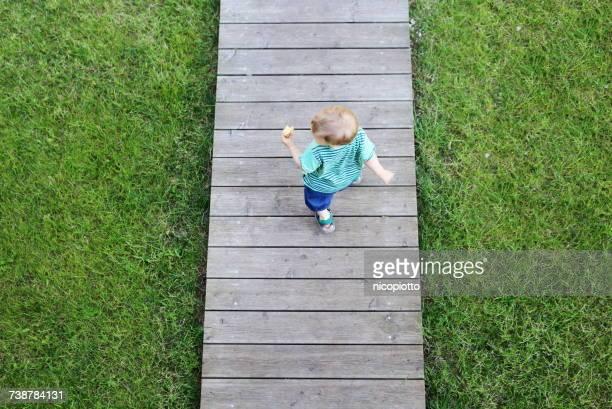 Overhead view of a boy walking along a wooden boardwalk