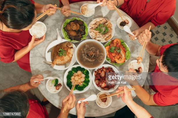overhead view of a chinese new year reunion dinner activity - chinese new year stock pictures, royalty-free photos & images