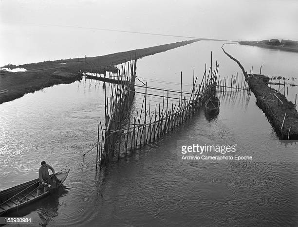Overhead view of a fisherman in a flatbottomed boat on a lagoon Comacchio Italy 1949