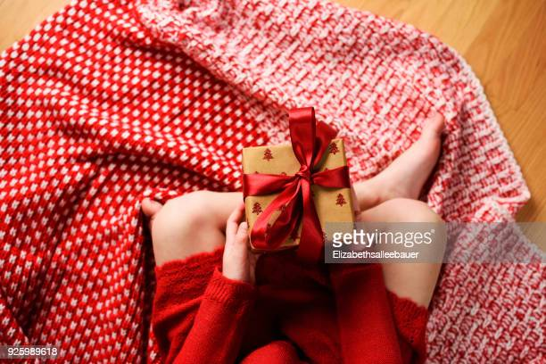 overhead view of a girl sitting cross-legged holding a wrapped christmas gift - bow legged stock photos and pictures