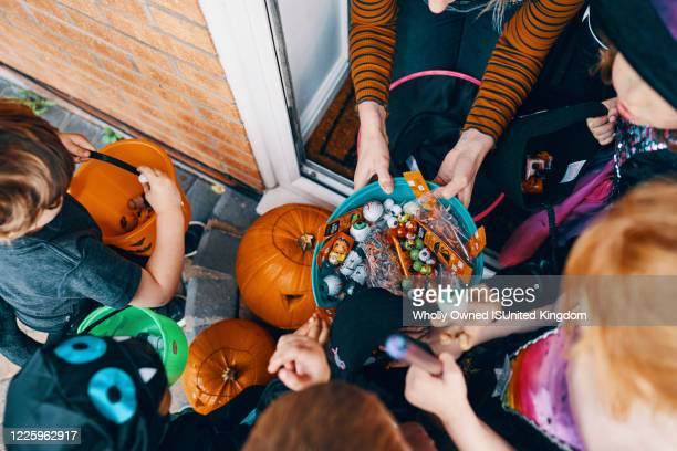 overhead view  of a group of children at a front door taking sweets from a bowl at halloween. - trick or treat stock pictures, royalty-free photos & images