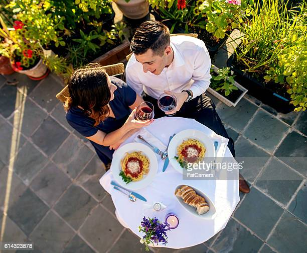 Overhead view of a heterosexual couple drinking wine at dinner