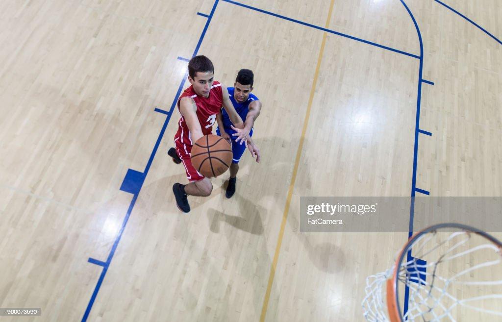 Draufsicht auf ein High-School-Basketball-Spieler versuchen, aus einem Tempogegenstoß Gäste : Stock-Foto