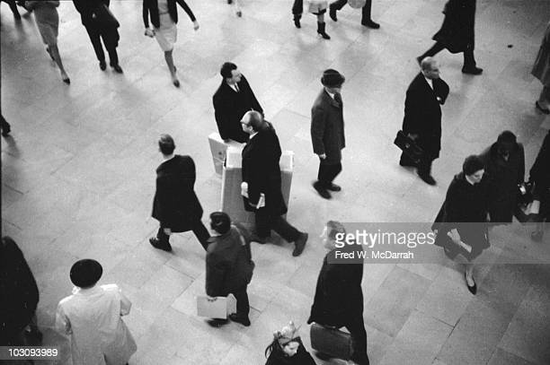 Overhead view of a man as he carries a large cardboard box past oblivious commuters in Grand Central Station as part of an art 'happening' New York...