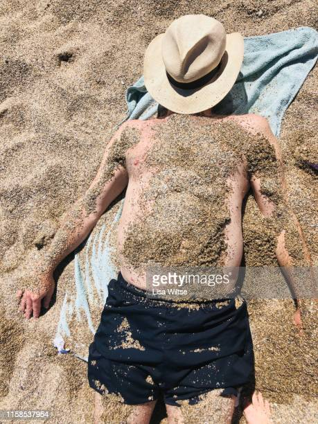 overhead view of a man covered in sand on the beach - enterrar imagens e fotografias de stock