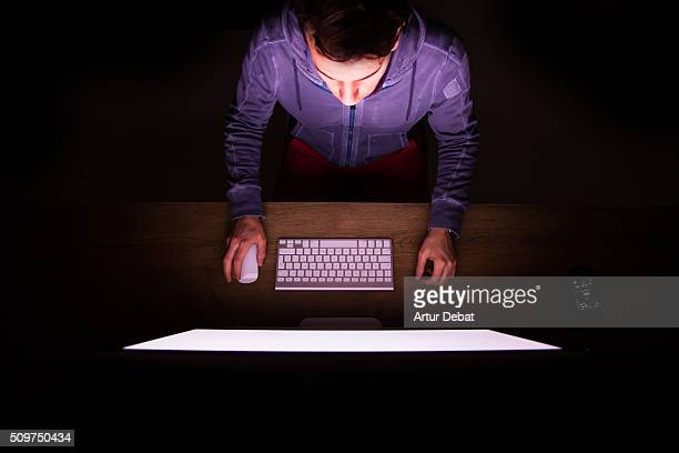 Overhead view of a man in front of bright computer working in the dark finishing work at midnight.
