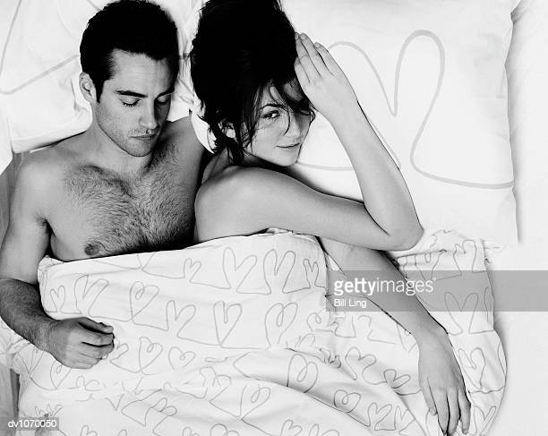 overhead view of a man sleeping in bed next to a woman who is looking at camera - 隣り合う ストックフォトと画像