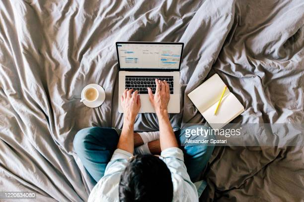 overhead view of a man working on a laptop from his bed at home - using laptop stock pictures, royalty-free photos & images