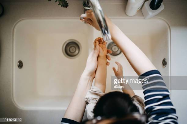 overhead view of a mother opening the tap for her little daughter and washing their hands together in the sink - antiseptic stock pictures, royalty-free photos & images