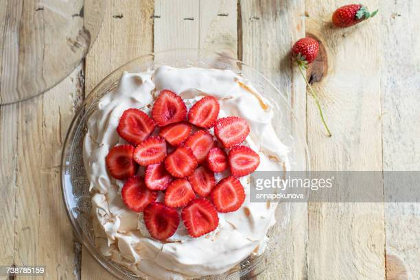 overhead view of a strawberry pavolva cake on wooden table - meringue stock pictures, royalty-free photos & images