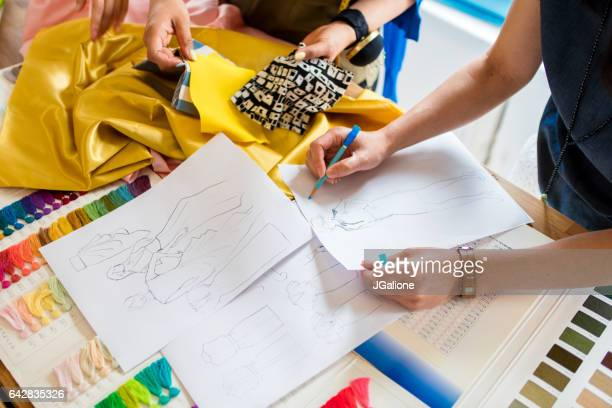 overhead view of a team of fashion designers working - jgalione stock pictures, royalty-free photos & images