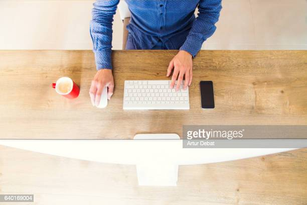 Overhead view of a tidy desk of a man working with computer and coffee in the morning with minimal and orthogonal view.