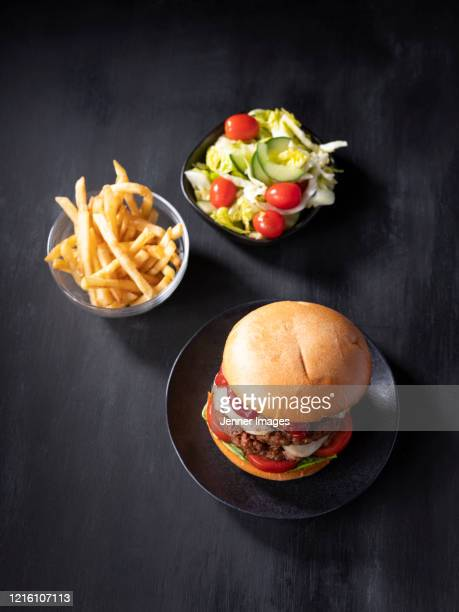overhead view of a vegan double cheeseburger meal. - burger stock pictures, royalty-free photos & images