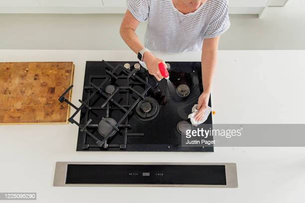 overhead view of a woman cleaning her gas hob - kitchen paper stock pictures, royalty-free photos & images