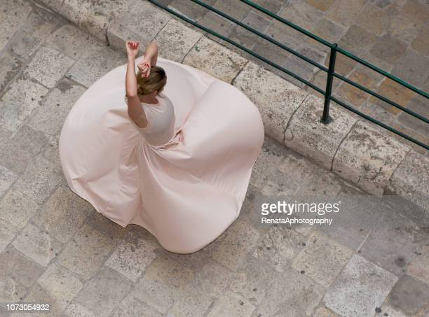 overhead view of a woman dancing in the street, valletta, malta - robe longue photos et images de collection