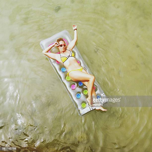 Overhead view of a woman lying on an inflatable mattress in the sea