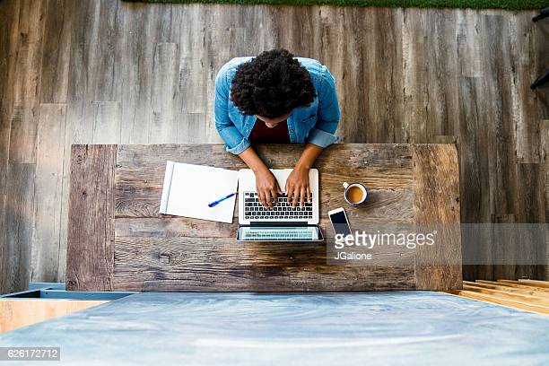 overhead view of a woman using a computer - sopra foto e immagini stock