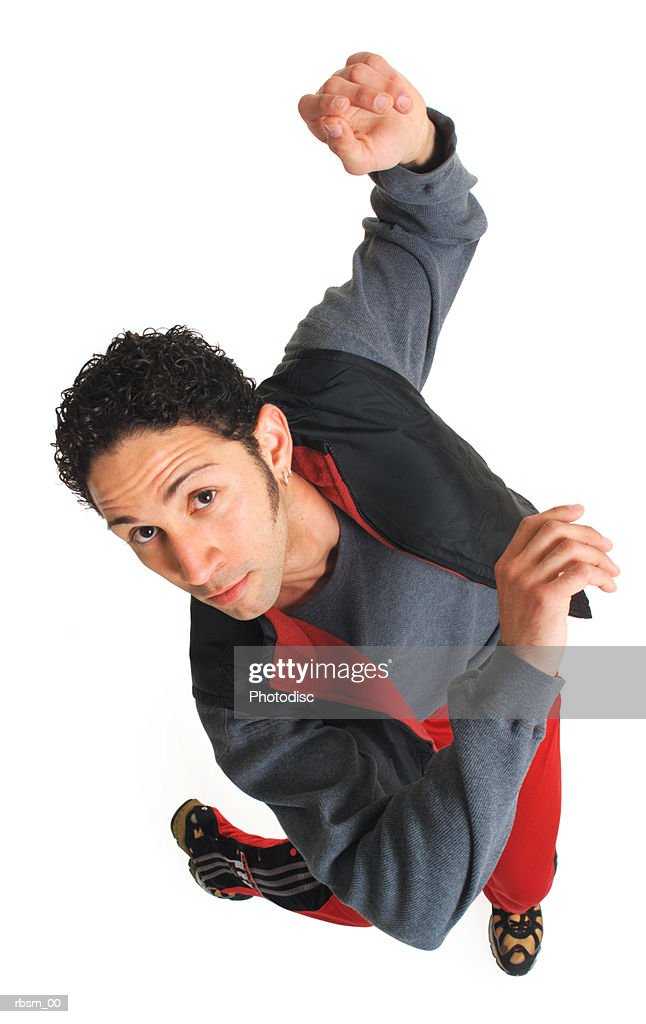 overhead view of a young hispanic man in red pants and a grey shirt raises his arms and dances while looking up at the camera : Foto de stock