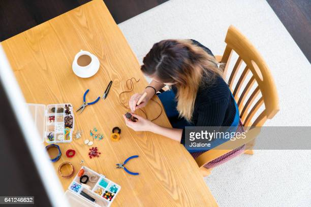 ジュエリーを作る若い女性のオーバー ヘッド ビュー - 宝飾品 ストックフォトと画像