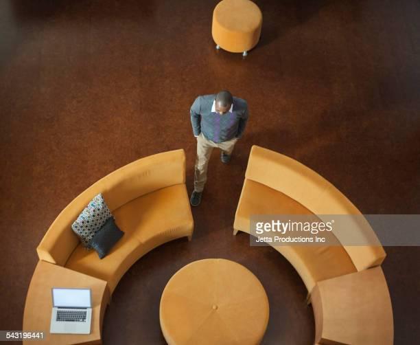 Overhead view of African American businessman near circular sofa