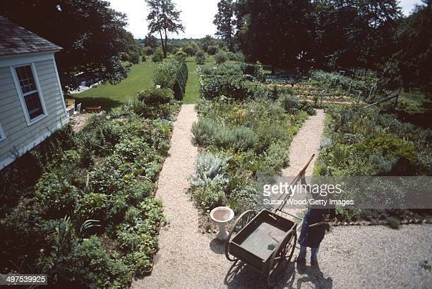 Overhead view of American businesswoman Martha Stewart as she collects gardening tools from a wheelbarrow on the grounds of her home Westport...