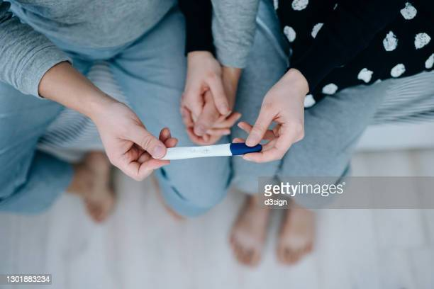 overhead view of an affectionate young asian couple sitting on the bed, holding hands and holding a positive pregnancy test together. it's finally happening. the long-awaited news. life events, fertility and family concept - pregnancy stock pictures, royalty-free photos & images