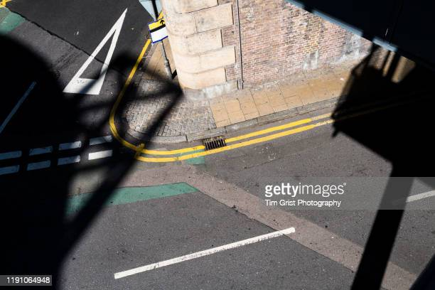 overhead view of an empty road junction in bright sunlight and partial shadow - urban road stock pictures, royalty-free photos & images