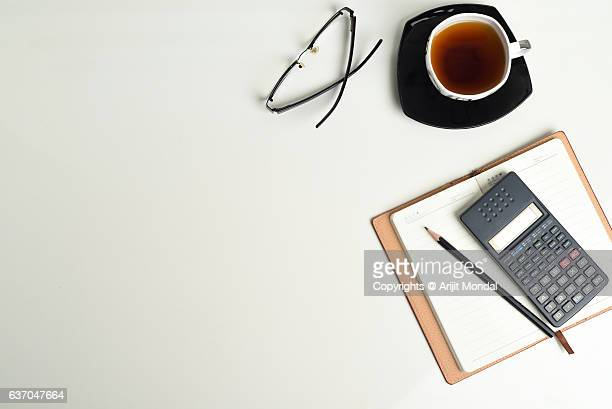 Overhead View Of An Office Desk With Calculator, Tea, Reading Glass, Notebook And Pencil
