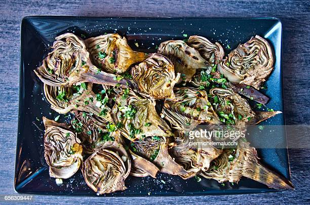 Overhead view of artichokes baked with oil, parsley and lemon