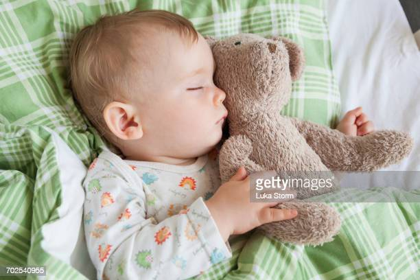 Overhead view of baby boy asleep on bed holding teddy bear