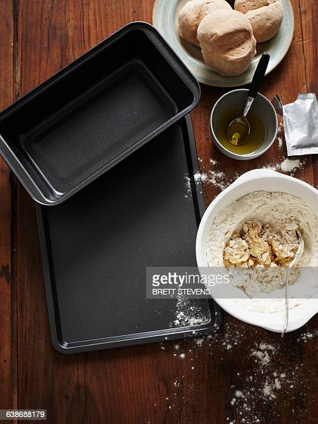 Overhead view of baking trays and bread mixture in mixing bowl