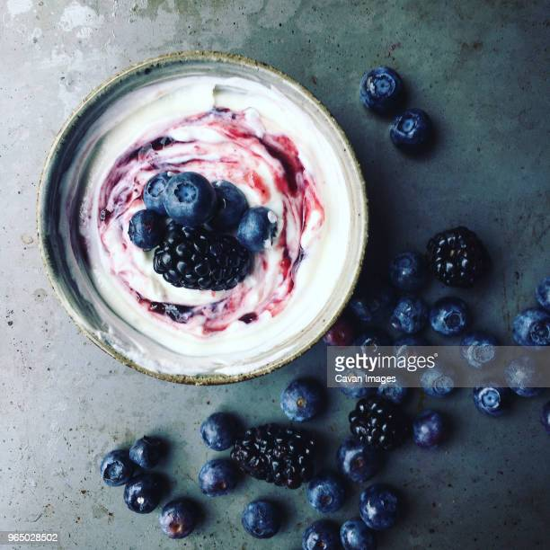 overhead view of berry fruits and syrup on yoghurt - yoghurt stock pictures, royalty-free photos & images