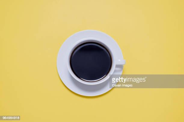 overhead view of black coffee in cup on yellow table - saucer stock pictures, royalty-free photos & images