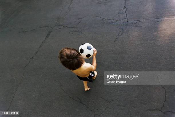 Overhead view of boy holding soccer ball while walking on street
