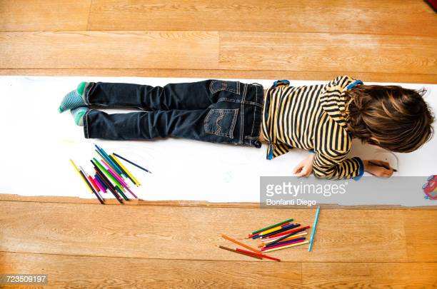 Overhead view of boy lying on top of and drawing on long paper