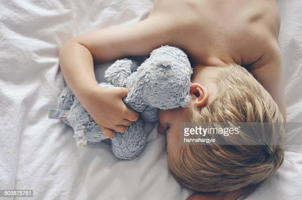 Overhead view of boy sleeping in bed with teddy bear