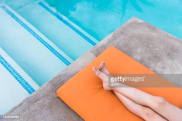 Overhead view of boys legs lying on poolside