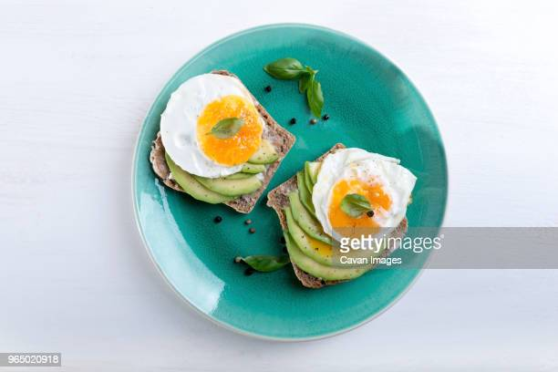 overhead view of breakfast served in plate on table - avocado toast stockfoto's en -beelden