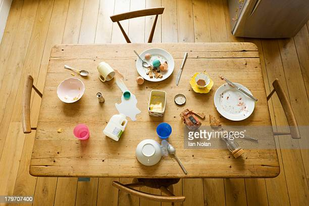 overhead view of breakfast table with eaten food and messy plates - 宴の後 ストックフォトと画像