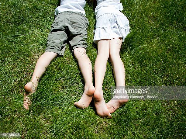 Overhead view of brother and sisters legs as they lay on grass