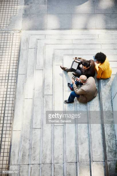 Overhead view of business colleagues discussing project on digital devices while sitting on building steps