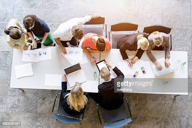 Overhead view of business team brainstorming at desk in office